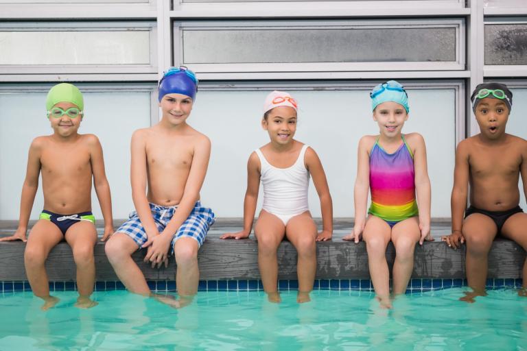 4 kids sitting on edge of swimming pool